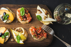 Bruschetta set with glass of white wine over dark background Royalty Free Stock Images