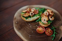 Bruschetta with prawn and avocado on a wooden board with arugula, sesame,tomatoes on wooden background for text, copy stock photos