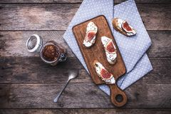 Bruschetta and Sliced figs on chopping board in rustic style Stock Photos