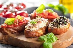Bruschetta, on slices of toasted baguette garnished with basil. stock images
