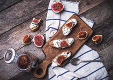 Bruschetta snacks with cut figs on napkin in rustic style Stock Photography