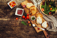 Bruschetta with soft cheese, tomatoes, sausage and herbs. Royalty Free Stock Photo