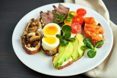 Bruschetta sorterade olika fyllningar, på plattor med ett löskokt ägg i mitt Royaltyfri Fotografi