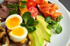 Bruschetta sorterade olika fyllningar, på plattor med ett löskokt ägg i mitt Fotografering för Bildbyråer