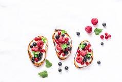 Bruschetta su un fondo leggero, vista superiore delle bacche Panini con formaggio cremoso, i lamponi, il rosso ed il ribes nero B immagini stock libere da diritti