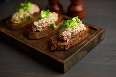 Bruschetta, sulle fette di baguette tostate guarnite con basilico Fotografie Stock