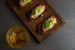 Bruschetta, sulle fette di baguette tostate guarnite con basilico Immagini Stock