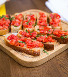 Bruschetta with sweet tomatoes and basil. A wooden plate with bruschettas in the restaurant Stock Image