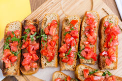 Bruschetta with sweet tomatoes and basil. A wooden plate with bruschettas in the restaurant Royalty Free Stock Photo