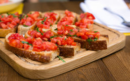 Bruschetta with sweet tomatoes and basil. A wooden plate with bruschettas in the restaurant Stock Images