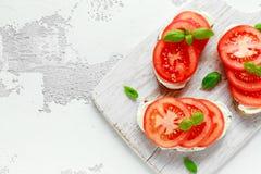 Bruschetta, Toast mit Weichkäse, Basilikum und Tomaten auf einem weißen hölzernen Brett Italienischer gesunder Snack, Lebensmitte lizenzfreies stockbild