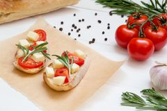 Bruschetta toasts with mozzarella, cherry tomatoes and fresh garden rosemary, close up stock images