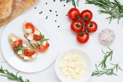 Bruschetta toasts with mozzarella, cherry tomatoes and fresh garden rosemary. Top view with space for your text royalty free stock image