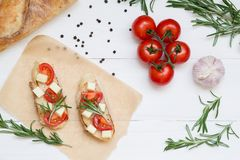 Bruschetta toasts with mozzarella, cherry tomatoes and fresh garden rosemary. Top view with space for your text royalty free stock images