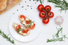 Bruschetta toasts with mozzarella, cherry tomatoes and fresh garden rosemary. Top view with space for your text stock images