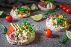 Bruschetta with tomato, avocado, herbs and arugula. Rustic background. Top view. Bruschetta with tomato, avocado, herbs and arugula. Rustic background stock photography