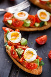 Bruschetta with tomato, avocado and quail egg Royalty Free Stock Image