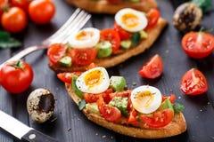 Bruschetta with tomato, avocado and quail egg Stock Image
