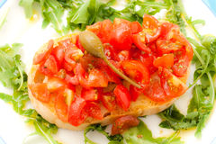 Bruschetta with tomato, basil and caper. Royalty Free Stock Images