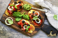 Bruschetta with tomato,black olives,capers and sauce pesto. Stock Photography