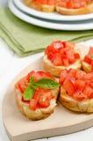 Bruschetta with tomato. Fresh bruschetta with tomato and basil on cutting board Royalty Free Stock Photography