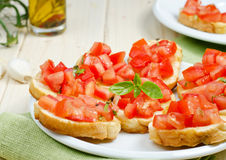 Bruschetta with tomato. Fresh bruschetta with tomato and basil on white plate Stock Image