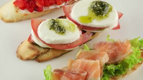 Bruschetta with tomato, mozzarella and salmon stock video