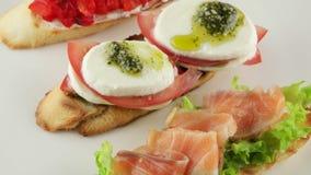 Bruschetta with tomato, mozzarella and salmon stock video