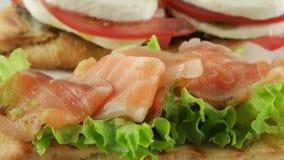 Bruschetta with tomato, mozzarella and salmon, closeup stock video footage