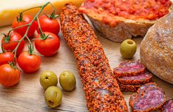 Bruschetta with tomato paste, tomatoes, cheese, olives and fuet. Royalty Free Stock Photo