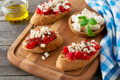 Bruschetta with tomatoes, feta cheese and basil. Traditional Greek snack on wooden background. Stock Photos