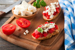 Bruschetta with tomatoes, feta cheese and basil. Traditional Greek snack on wooden background. Royalty Free Stock Photos