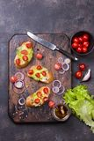 Bruschetta with tomatoes, herbs and oil on toasted garlic bread. Bruschetta with tomatoes, herbs, onion and olive oil on toasted garlic bread. Dark cutting board Royalty Free Stock Photography