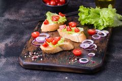 Bruschetta with tomatoes, herbs and oil on toasted garlic bread. Bruschetta with tomatoes, herbs, onion and olive oil on toasted garlic bread. Dark cutting board Royalty Free Stock Photos