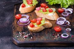 Bruschetta with tomatoes, herbs and oil on toasted garlic bread. Bruschetta with tomatoes, herbs, onion and olive oil on toasted garlic bread. Dark cutting board Royalty Free Stock Images