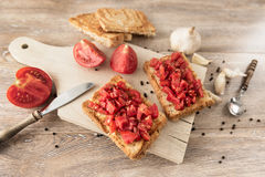 Bruschetta with tomatoes on rustic, old wood background Royalty Free Stock Images