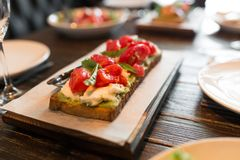 Bruschetta with tomatos served on wooden stand royalty free stock photography