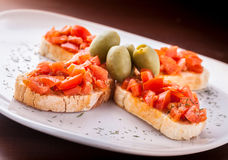 Bruschetta tost sandwich on white plate. Bruschetta tost sandwich whit tomato pesto and olives on white plate and dark background Royalty Free Stock Photo
