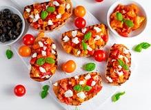 Bruschetta tradicional saboroso do tomate com cobertura do queijo de feta, manjericão fresca Imagem de Stock Royalty Free