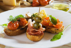 Bruschetta, traditional italian toasted bread. With tomato, olives and prosciutto Royalty Free Stock Image