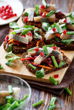 Bruschetta `vinaigrette` on rye bread with herring. Bruschetta on rye bread with fried straws of beet and carrots, greens and slices of herring on a bamboo royalty free stock images