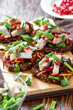 Bruschetta `vinaigrette` on rye bread with herring. Bruschetta on rye bread with fried straws of beet and carrots, greens and slices of herring on a bamboo royalty free stock image