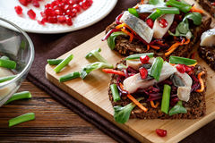 Bruschetta `vinaigrette` on rye bread with herring. Bruschetta on rye bread with fried straws of beet and carrots, greens and slices of herring on a bamboo stock photography