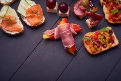 Bruschetta z łososia, ogórka, pomidoru, basilu i mozzarelli serem na drewnianej desce, Tradycyjna włoszczyzna fotografia stock