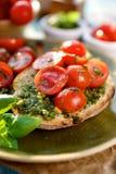 Bruschetta z świeżymi czereśniowymi pomidorami i aromatycznym zielarskim pesto Obraz Stock