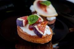 Bruschetta z koźlim serem i figami na czarnym talerzu Fotografia Stock