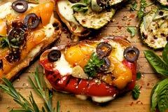 Bruschetta z pieprzami, serem, oliwkami i ziele na drewnianej desce piec na grillu, Zdjęcia Royalty Free