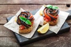 2 bruschettas с испеченными aubergines и перцами на деревянной доске, деревенском стиле Стоковая Фотография