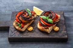 2 bruschettas с испеченными aubergines и перцами на черной предпосылке Стоковые Фотографии RF