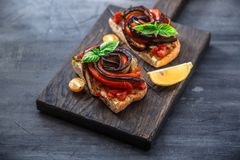 2 bruschettas с испеченными aubergines и перцами на черной предпосылке Стоковое Изображение RF